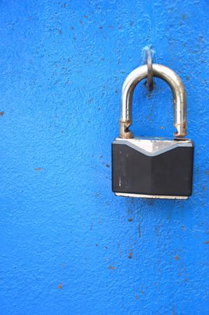 black padlock on the blue metal door