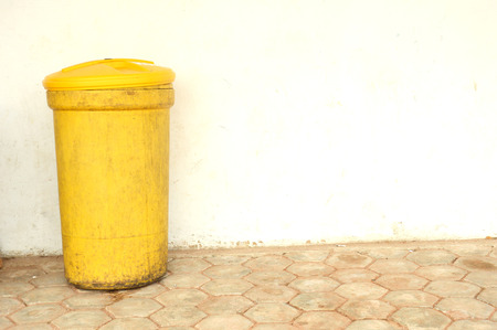 plactic: a yellow plactic trash can against the wall
