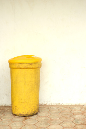 a yellow plactic trash can against the wall