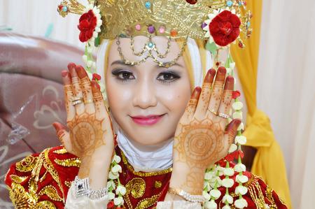 jilbab: Beautiful Indonesian bride dressed in traditional red banjarnese costume
