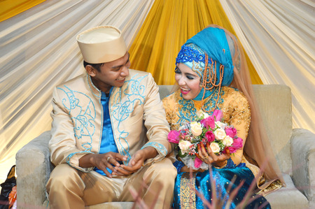 Indonesian bridal couples were dressed in traditional modern moslem bridal costume photo