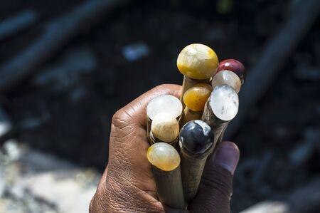 bamboo stick: male hand hold batu akik or natural gemstone on the bamboo stick