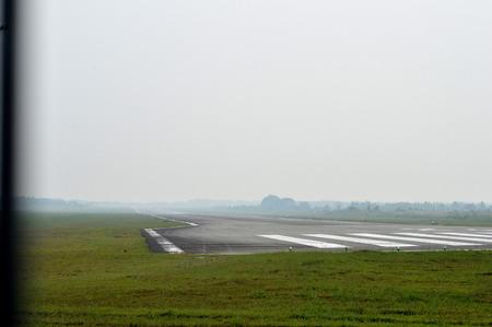 runways: TARAKAN, INDONESIA - SEPT, 10, 2015 : view on the Juwata International airport runways  that look Tarakan city cloaked in thick smog on Sept 10, 2015  in Tarakan, Indonesia