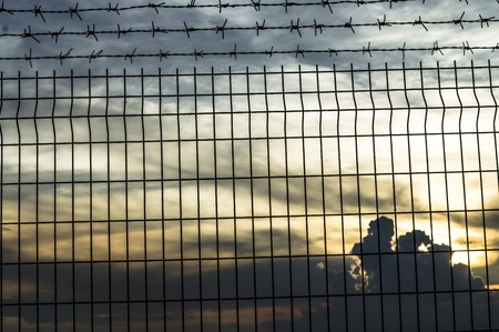 galvanised: iron wire fence against twilight sky Stock Photo