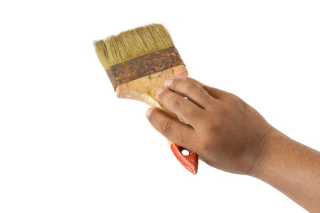 blue background: male hand holding an old paint brush on white background Stock Photo