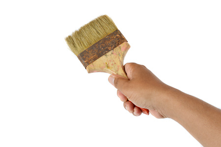 artistic background: male hand holding an old paint brush on white background Stock Photo