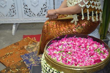 wedding customs: flower petals in water with golden scoop in used in Javanese Indonesia  traditional wedding ceremony