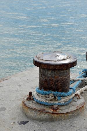 mooring bollard: Rusty mooring bollard with ship ropes on seaport Stock Photo