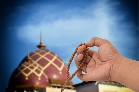 Muslim male hands holding rosary with mosque blurry background