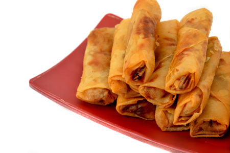 lumpia Semarang or Spring Rolls containing bamboo shoots and chicken on red plate at white background Stock Photo