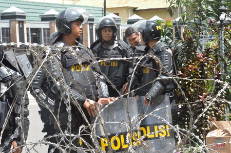 controversial: TARAKAN,Indonesia-April 7, 2016. police guard on demonstration of the electricity crisis at the building of parliament in Tarakan city Editorial