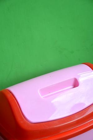 pink plastic bins on the green wall