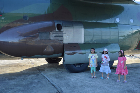 TARAKAN, INDONESIA. March, 10,  2017. Three daughters watched Hercules military airplane at the static show Sukhoi aircraft of the Indonesian Air Force on cornerstone of the air force shelter Tarakan City Indonesia Editorial