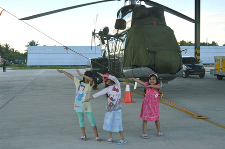 cornerstone: TARAKAN, INDONESIA. March, 10,  2017. theree daughters watched static show Sukhoi aircraft of the Indonesian Air Force on cornerstone of the air force shelter Tarakan City Indonesia Editorial