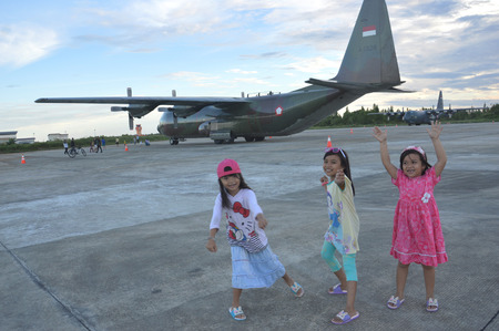 airfield: TARAKAN, INDONESIA. March, 10,  2017. Three daughters watched Hercules military airplane at the static show Sukhoi aircraft of the Indonesian Air Force on cornerstone of the air force shelter Tarakan City Indonesia Editorial