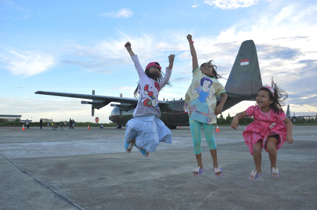 cornerstone: TARAKAN, INDONESIA. March, 10,  2017. Three daughters watched Hercules military airplane at the static show Sukhoi aircraft of the Indonesian Air Force on cornerstone of the air force shelter Tarakan City Indonesia Editorial