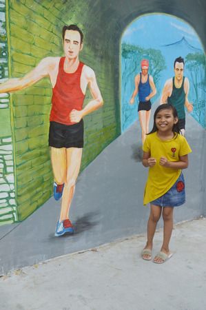 TARAKAN, INDONESIA - 5th August  2017 : the little girls pose on the three-dimensional mural painting on the cement wall Editorial