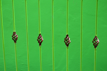 iron fence on the green wall  Stock Photo