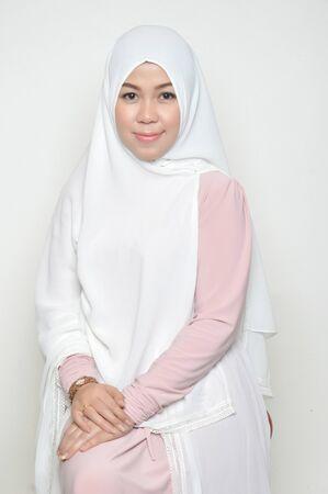portrait of a beautiful muslim woman wearing a headscarf on white background Stockfoto
