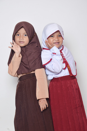 two asian little girl with primary school uniform and girl scout uniform