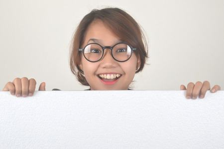 cheerful asian girl with a white board isolated on white background