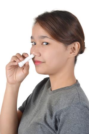 Chica asiática tiene inhalador nasal aislado sobre fondo blanco. Foto de archivo
