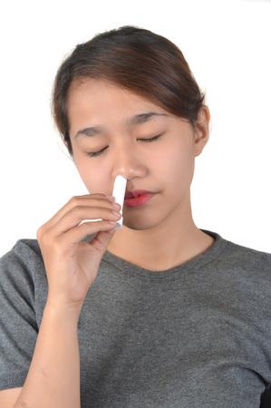Chica asiática tiene inhalador nasal aislado sobre fondo blanco.