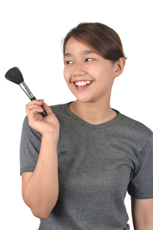 Asian girl holds a makeup brush isolated on white background