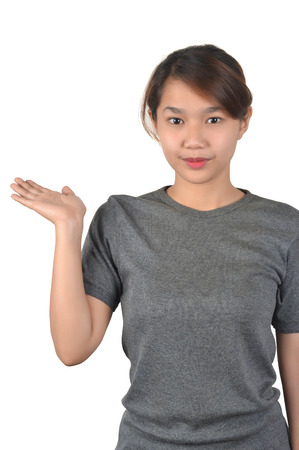 Beautiful young woman wearing a gray shirt presenting something on her hand isolated on white