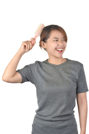 Asian girls in casual shirts combing their hair on white background Stock Photo