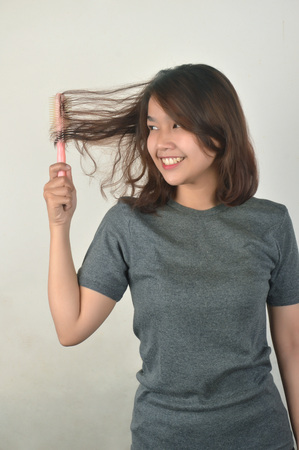 Asian girls in casual shirts combing their hair on white background Reklamní fotografie