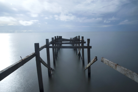 the ruins of a wooden bridge on the edge of the sea