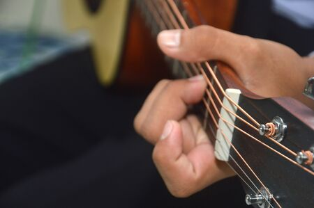 man's fingers playing a classical wooden guitar string