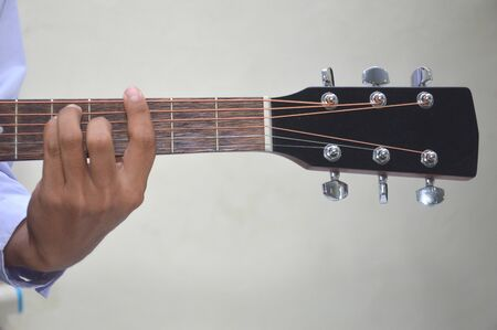 man's fingers playing a classical wooden guitar string Banco de Imagens
