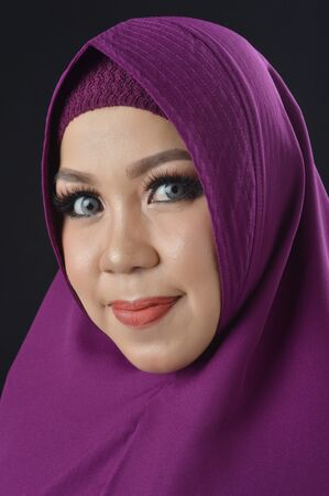 portrait of a beautiful muslim woman wearing a violet headscarf isolated on black background