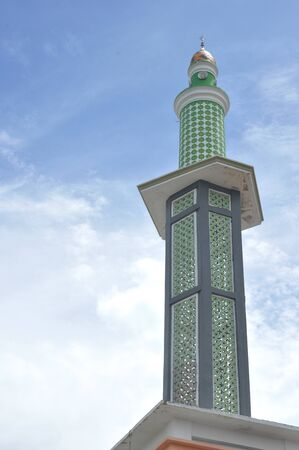 mosque tower against blue sky adn white clouds
