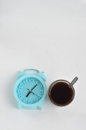 A glass of black coffee and a blue alarm clock isolated on white background, coffee time concept