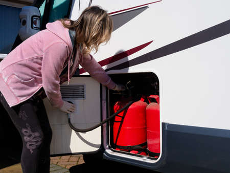A lady checks her gas bottles in a locker on her recreational vehicle.Motorhome Reklamní fotografie