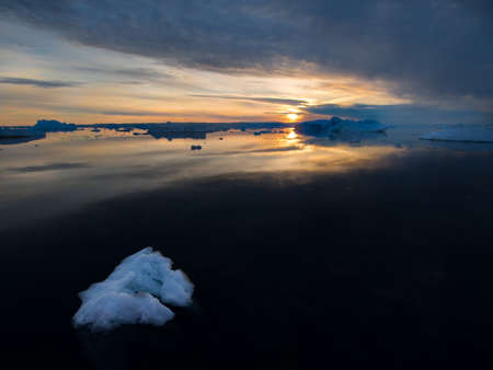A piece of broken ice in foreground drifts in a dark black sea as a sun sets on the horizon amongst icebergs cause by global warming.Greenland Arctic.Image