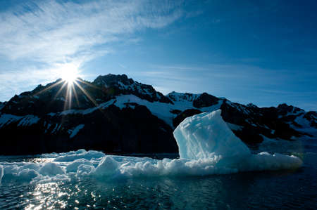 A sun bursts over arctic mountains casting sunlight onto an iceberg which is breaking down due to climate warming.Climate crisis and emergency breakdown.Image