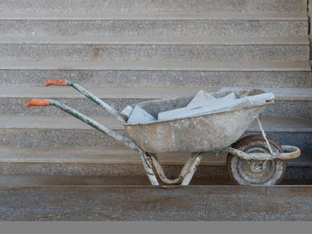 A wheelbarrow covered in grey stone dust contains grey stone tiles and stands in front of grey steps.It has orange contrasting handles.Image
