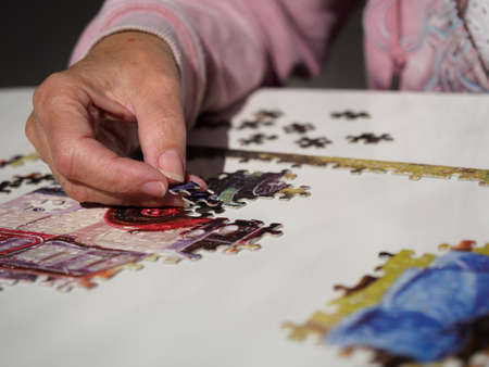 Close view of a female hand with jigsaw piece about to be placed into a puzzle on white table.Lockdown activity.Image