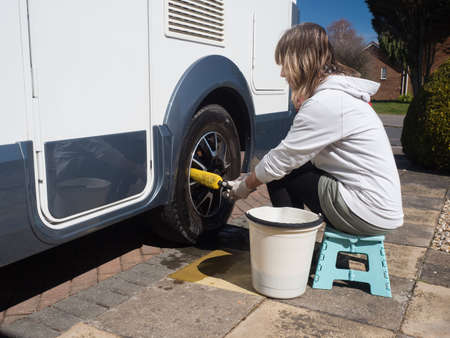 A lady motorhome owner cleans the wheels with a yellow wheel brush.She has a bucket beside her as she sits on a stool