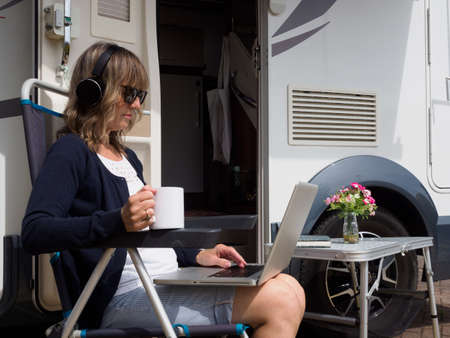 A lady sits outside her home and recreational vehicle with her laptop and headphones.She holds a mug.Flowers and a book are on a table beside her.Stay at home