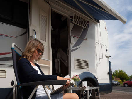 A lady motorhome owner sits in a camping chair with headphones and laptop outside her recreational vehicle.She has a mug in her hand.Flowers and book are on a table Reklamní fotografie
