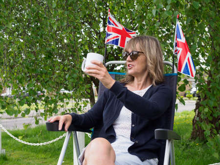 A lady sits in a camping chair in her garden and gestures cheers with a mug in her hand.Two union jack flags are behind her in the garden with tree in background.