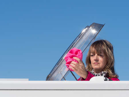 A lady motorhome owner cleans the skylight hatch of her vehicle with a pink cloth.Head and shoulders are visible as she has climbed through the roof skylight.Copy Space