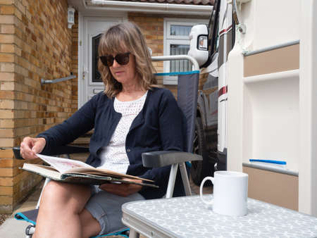 A lady sits outside he r house and motorhome parked reading a book and a white mug on table beside her.Stay at home.Recreational Vehicle Reklamní fotografie