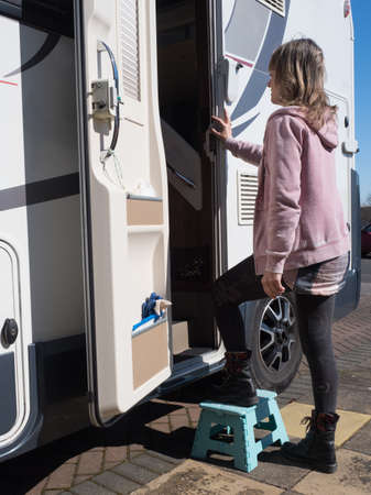 A lady motorhome owner uses a small step to enter her motorhome using the side habitation door.Vertical Image