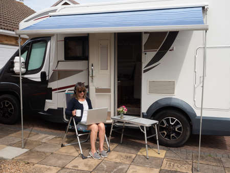 A lady motorhome owner is parked on her drive unable to travel due to Coronavirus lockdown.She has laptop headphones and mug sat on camping chair under awning of her recreational vehicle Stockfoto